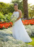 Bride in garden. A beautiful smiling bride standing in a garden holding bouquet Royalty Free Stock Photos