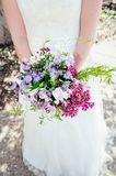 A bride holds a bouquet of purple and pink wildflowers stock photos