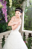 Bride in garden with white dress, summer. Brunette. Crossing her arms Stock Photo