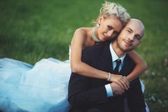 Bride gently embraces the groom sitting on the lawn. Young beautiful bride gently embraces the groom in a suit sitting on the lawn in summer Stock Photo