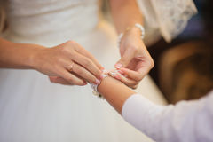 Bride getting bracelet dressed Stock Photography