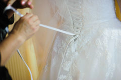 Bride getting dressed on her wedding day Stock Images