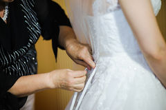 Bride getting dressed on her wedding day Stock Image