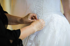 Bride getting dressed on her wedding day Stock Photography