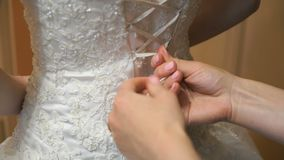 Bride getting dressed up for the wedding. Close-up of hands of young woman friend tying white ribbons of a corset wedding bridesmaid dresses stock video
