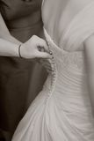 Bride Getting Ready. On her wedding day having dress buttoned Stock Photo