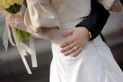 Bride girdling groom's waist Stock Photo