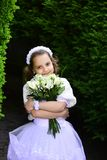 Bride girl, bridesmaid and wedding ceremony. Wedding fashion, beauty salon. Fashion, Cinderella, princess. Little girl in white dress with rose flower bouquet stock photo