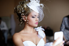 Bride girl in wedding dress looking in mirror Stock Images