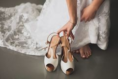 The bride, girl or young woman in a beautiful elegant modern stylish wedding dress reaches for light fashionable high-heeled shoes royalty free stock photography