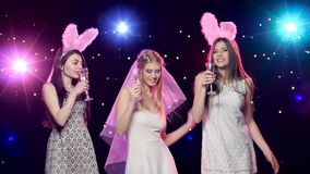 Bride, girlfriends dancing, drinking champagne blowing kisses at bachelorette party. Happy bride with girlfriends dancing, drinking champagne and making blowing stock video