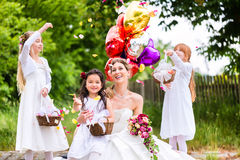 Bride with girls as bridesmaids, flowers and balloons Royalty Free Stock Images