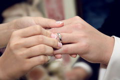 Bride giving an engagement ring to her groom Stock Photos