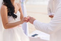 Bride giving an engagement ring to her groom under the arch deco royalty free stock image
