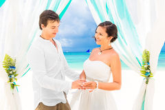 Bride giving an engagement ring to her groom under the arch deco Royalty Free Stock Photography