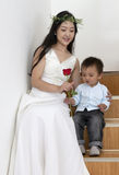 Bride giving son a rose. A Chinese bride dressed in her wedding dress gives her young son a red rose while sitting on the stairs Royalty Free Stock Photos