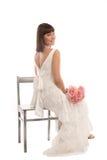 Bride glances over her shoulder. Cheerful sitting bride with roses glances over her shoulder Stock Photo