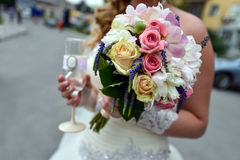 Bride with a glass of champagne and a bouquet of flowers at the wedding ceremony Stock Photos