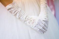 Bride gloves. Over white dress closeup shot Royalty Free Stock Photo
