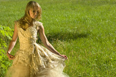 Bride in a golden colored wedding dress stock image