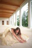 Bride in golden gown on floor Stock Photography