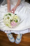 Bride in gown and tennis shoes stock image