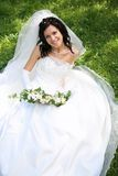 Bride on the grass. Portrait of fashion bride with bunch of flowers sitting on the grass Royalty Free Stock Photo
