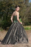 Bride in green dress. Shot from side; bride in green dress holding flower royalty free stock photo