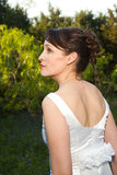 Bride in green field. A woman with dark hair in a wedding gown looks away Stock Photo