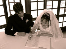 Bride and Groom. Sepia image of a Bride and Groom signing the marriage register royalty free stock photos