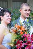 Bride and groom. Smiling bride and groom portrait with flowers Royalty Free Stock Photos