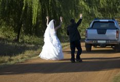 Bride and Groom. Trying to pull over a vehicle with arms waving in the air Stock Images