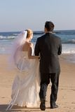 Bride & Groom. Bride and groom walking on the beach, just married Royalty Free Stock Photo