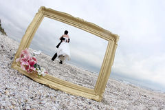 Bride and groom. Wedding couple and a photo frame on the beach Royalty Free Stock Photography