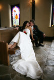 Bride and groom. Attractive bride and groom sitting in church pews kissing Royalty Free Stock Images