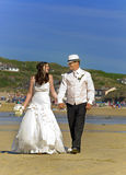 Bride and Groom. Walking on the beach shortly after being married in Perranporth, cornwall Royalty Free Stock Images