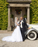 Bride and Groom. A stunning looking bride and groom next to a vintage wedding car Stock Image