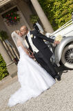 Bride and Groom. A stunning looking bride and groom next to a vintage wedding car Stock Photography