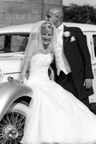 Bride and Groom. A stunning looking bride and groom next to a vintage wedding car Stock Photos