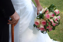 Bride and Groom. Groom with a cane and bride with a white and pink rose bouquet stock photos