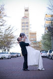 Bride and Groom. Vertical image of a bride and groom kissing in the middle of a brick street royalty free stock images