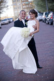 Bride and Groom. Vertical image of a groom holding a bride in the middle of a city street royalty free stock photos