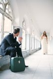 Bride and groom. Groom with a suitcase waiting for his bride to come stock photo
