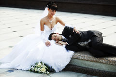 Bride and groom. Bride sitting and groom laying royalty free stock photography