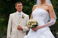 Bride and groom. Bride holding bouquet and groom on the background stock photos