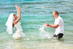 Bride and groom. Making splash in the sea royalty free stock images