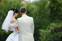 Bride and groom. Groom and bride embrace one another in the park royalty free stock images