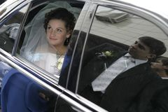 Bride and groom. The young bride in a veil and with a bouquet looks out of a window of a limousine on the groom who is reflected in the next window royalty free stock images