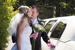 Bride and groom. Kissing by a wedding car limousine Stock Photo