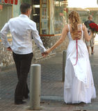Bride and groom. Walking hand in hand in the street royalty free stock photography